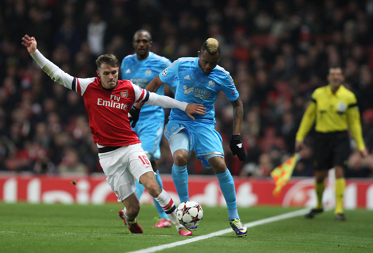 Arsenal's Aaron Ramsey despite the attentions of  Marseille's Jordan Ayew<br /> Photo by Kieran Galvin/CameraSport<br /> <br /> Football - UEFA Champions League Group F - Arsenal v Marseille - Tuesday 26th November 2013 - The Emirates Stadium - London<br /> <br /> &copy; CameraSport - 43 Linden Ave. Countesthorpe. Leicester. England. LE8 5PG - Tel: +44 (0) 116 277 4147 - admin@camerasport.com - www.camerasport.com