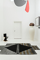 The entrance hall holds an eclectic display of pieces such as a Philippe Starck Miss Flower Power vase and the severely modernist Zigzag chair by Gerrit Rietvels. Overhead are petal-shaped mobiles in the tradition of Alexander Calder by Dutch design studio GramFratesi.
