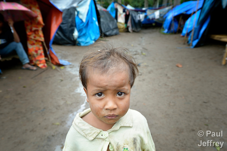 This boy is one of several dozen residents of the indigenous village of San Fernando who fled their home on March 14, shortly after the March 5 assassination of Jimmy Liguyon, their baranguay captain. Liguyon was killed by a paramilitary squad led by Aldy Salusad, which was angered by Liguyon's refusal to sign papers ceding the community's land to a large mining company. Convinced they were also in danger from Salusad and his military allies, community members fled to the provincial capital of Malaybalay, where they have set up temporary shelters on the grass in front of provincial offices. They promise not to leave until there is justice in the killing of Liguyon..