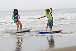 Stinson Beach, CA Siblings, ages six and eight, experimenting with riding boogie boards during beach vacation.  MR