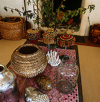 A collection of ethnic objects is displayed on the coffee table in the living room