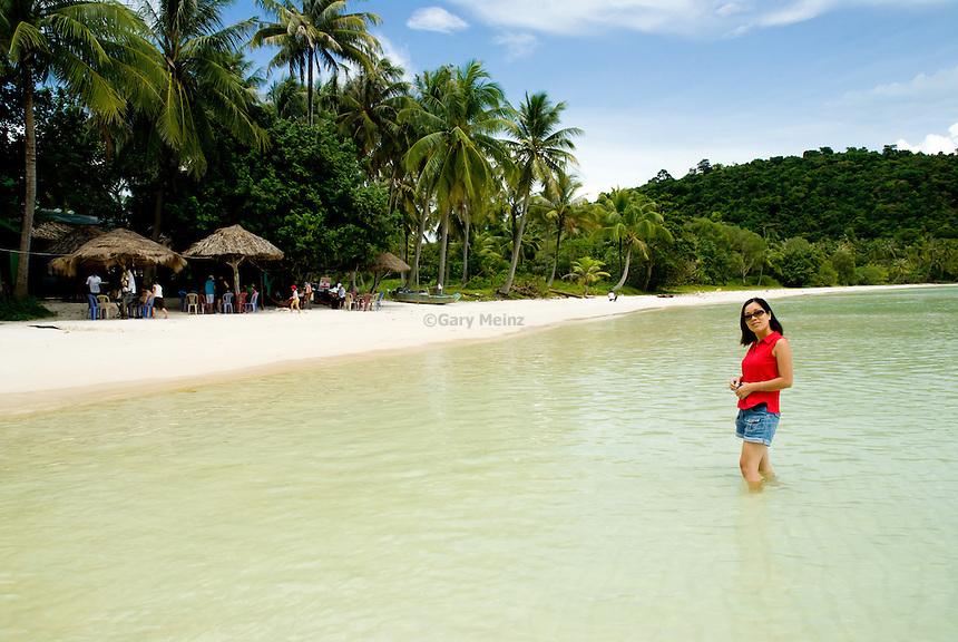 VIetnamese woman wading off sandy beach, Phu Quoc Island Vietnam