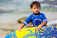 Young Local Hawaiian boy standing on the beach holding bodyboard  on Oahu, Hawaii