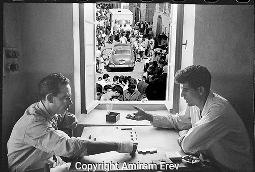 Two men playing dominoes with view out to the street through a window