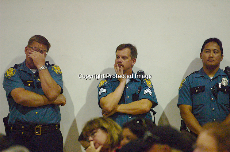 Seattle Police Department Southwest Precinct officers listen during a public meeting to discuss the stabbing of an area resident and crime in the area, at the South Park Community Center in Seattle Monday July 20, 2009.