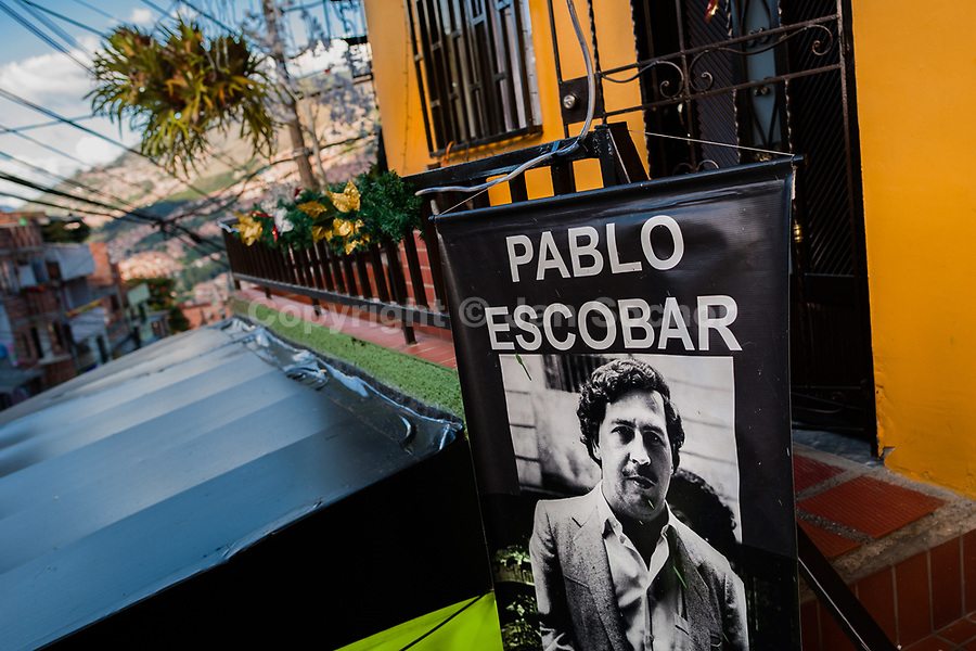 """A banner, depicting the drug lord Pablo Escobar, is seen hung above a barber shop in the Pablo Escobar neighborhood, Medellín, Colombia, 6 December 2017. Twenty five years after Pablo Escobar's death, the legacy of the Medellín Cartel leader is alive and flourishing. Although many Colombians who lived through the decades of drug wars, assassinations, kidnappings, reject Pablo Escobar's cult and his celebrity status, there is a significant number of Colombians who admire him, worshipping the questionable """"Robin Hood"""" image he had. Moreover, in the recent years, the popular """"Narcos"""" TV series has inspired thousands of tourists to visit Medellín, creating a booming business for many but causing a controversial rise of narco-tourism."""