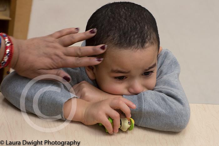 Education Preschool classroom scenes closeup of sad boy teacher's hand stroking his forehead separation at start of school year