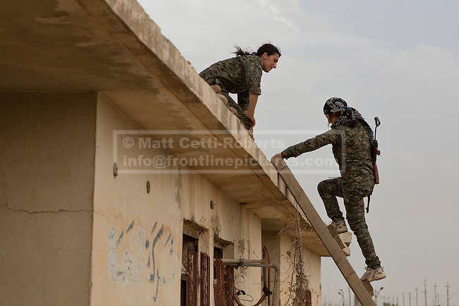 28/09/2014. Rabia, Iraq. Two female fighters belonging to the Syrian-Kurdish YPJ are seen on a roof top position in the Iraqi border town of Rabia.<br /> <br /> Facing each other across the Iraq-Syria border, the towns of Al-Yarubiyah, Syria, and Rabia, Iraq, were taken by Islamic State insurgents in August 2014. Since then The town of Al-Yarubiyah and parts of Rabia have been re-taken by fighters from the Syrian Kurdish YPG. At present the situation in the towns is static, but with large exchanges of sniper and heavy machine gun fire as well as mortars and rocket propelled grenades, recently occasional close quarter fighting has taken place as either side tests the defences of the other.