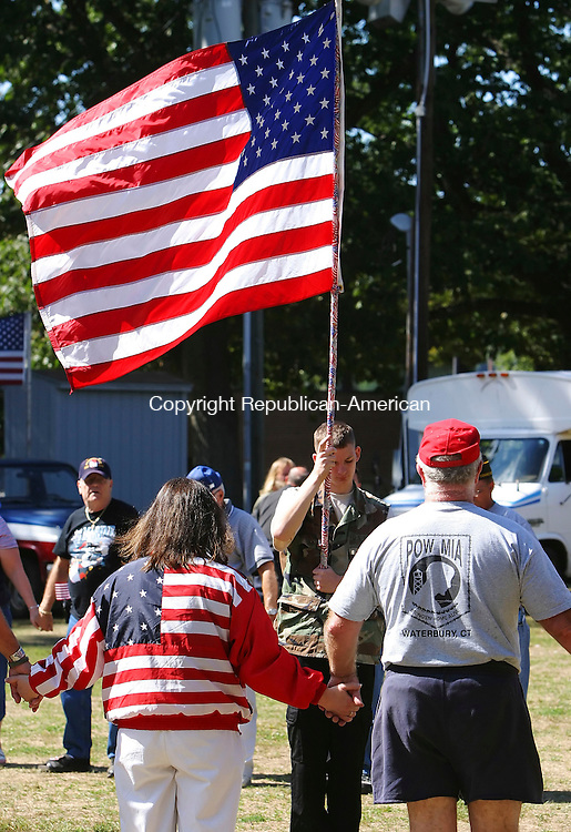 WATERBURY, CT- 10 SEPTEMBER 2005-091005BZ05-  Tyler Gode, of Cheshire, holds an American Flag inside a ring of veterans and friends  during a ceremony honoring prisoners of war and those missing or killed in action.  The Wheeler-Young VFW Post 201 and the Greater Waterbury POW/MIA Committee.<br /> Jamison C. Bazinet / Republican-American