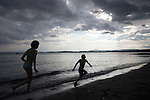 Silhouetted children playing at Paradise beach, Bygdoy, Oslo.