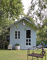 This rustic shed-cum-summer house makes a perfect bolthole at the bottom of the garden