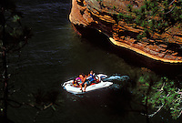 BOATERS EXPLORE THE SEA CAVES AT SQUAW POINT IN THE APOSTLE ISLANDS NATIONAL LAKESHORE NEAR BAYFIELD, WISCONSIN.