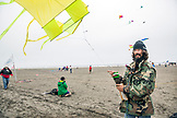 USA, Washington State, Long Beach Peninsula, International Kite Festival, man and his dog fly a kite