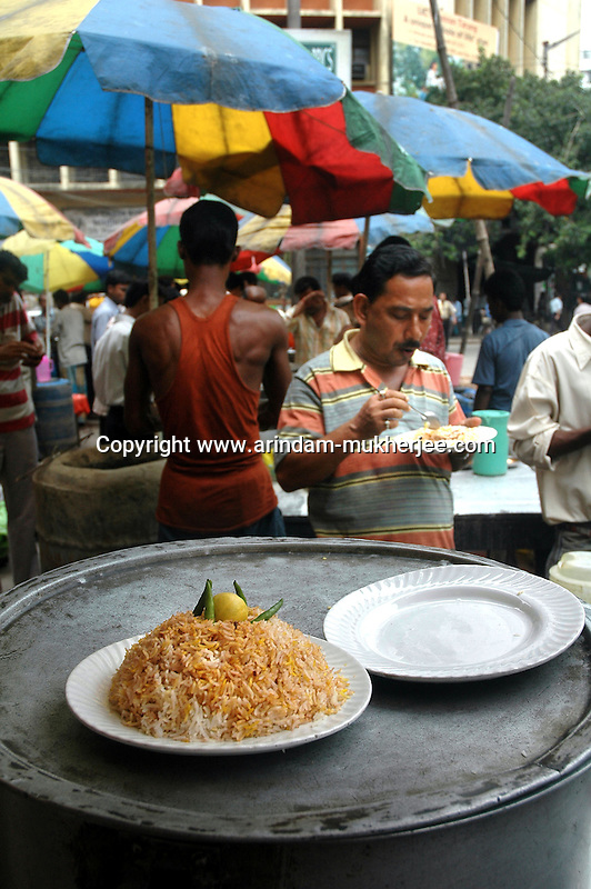 An Office worker having Biriyani at a street Biriyani stall during lunch break  in Dalhousie area of Kolkata. Street food stalls are serving the office goers for decades. All kind of Indian foods are available on the street at an affordable price. They sale them openly. Street food stalls are another results of unempoloyment and over poppulation. They serve millions of people in India. Kolkata, West Bengal,  India  7/18/2007.  Arindam Mukherjee/Landov