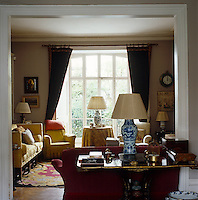 A wooden occasional table and a sofa partition the dining room from the adjoining sitting room