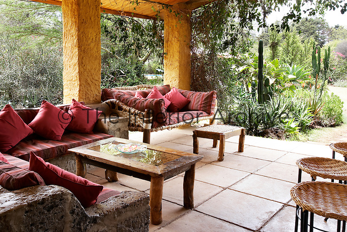 Seating on a covered stone terrace area of a luxury guest house lodge, which has a rustic feel. The talents of regional artists provide many of the finishing touches. Red striped cushions are placed on the stone and wicker sofas, which give a view to the garden.