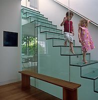 Twins, Clara and Hugo, walk down the glass staircase which forms part of the 'band of glass' that separates the old and new parts of the house