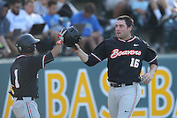 Gabe Clark (16) of the Oregon State Beavers is greeted by teammate Christian Donahue (1) after hitting a home run during a game against the UCLA Bruins at Jackie Robinson Stadium on April 4, 2015 in Los Angeles, California. UCLA defeated Oregon State, 10-5. (Larry Goren/Four Seam Images)