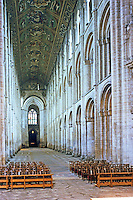 Ely: Ely Cathedral--Nave looking west. Nave has 13 bays. Norman columns rising 72 ft. to roof. The ceiling was always wood. Painted 1858-65. Reference only.