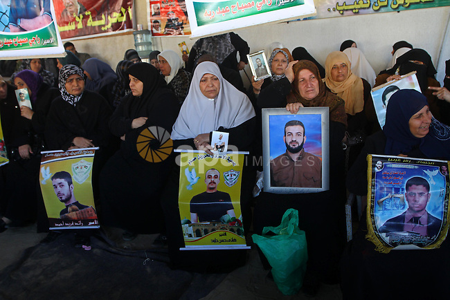 Palestinian women hold pictures of jailed relatives during a protest calling for the release of Palestinian prisoners from Israeli jails at the Red Cross office in Gaza City on Jan. 10,2011. Photo by Ashraf Amra