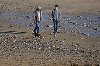 WEATHER PICTURE WALES<br /> Dog Walkers on the beach during the unusually warm weather in Langland Bay near Swansea, Wales, UK. Wednesday 27 February 2019