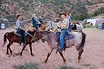 """Aug 9, 2008 -- COLORADO CITY, AZ:   Members of the Jessop family, a polygamist family and members of the FLDS, work with their horses in a corral behind their home in Colorado City, AZ. Colorado City and neighboring town of Hildale, UT, are home to the Fundamentalist Church of Jesus Christ of Latter Day Saints (FLDS) which split from the mainstream Church of Jesus Christ of Latter Day Saints (Mormons) after the Mormons banned plural marriage (polygamy) in 1890 so that Utah could gain statehood into the United States. The FLDS Prophet (leader), Warren Jeffs, has been convicted in Utah of """"rape as an accomplice"""" for arranging the marriage of teenage girl to her cousin and is currently on trial for similar, those less serious, charges in Arizona. After Texas child protection authorities raided the Yearning for Zion Ranch, (the FLDS compound in Eldorado, TX) many members of the FLDS community in Colorado City/Hildale fear either Arizona or Utah authorities could raid their homes in the same way. Older members of the community still remember the Short Creek Raid of 1953 when Arizona authorities using National Guard troops, raided the community, arresting the men and placing women and children in """"protective"""" custody. After two years in foster care, the women and children returned to their homes. After the raid, the FLDS Church eliminated any connection to the """"Short Creek raid"""" by renaming their town Colorado City in Arizona and Hildale in Utah. A member of the Jessop family weeds the community corn plot in Colorado City, AZ. The Jessops are a polygamous family and members of the FLDS. Photo by Jack Kurtz / ZUMA Press"""