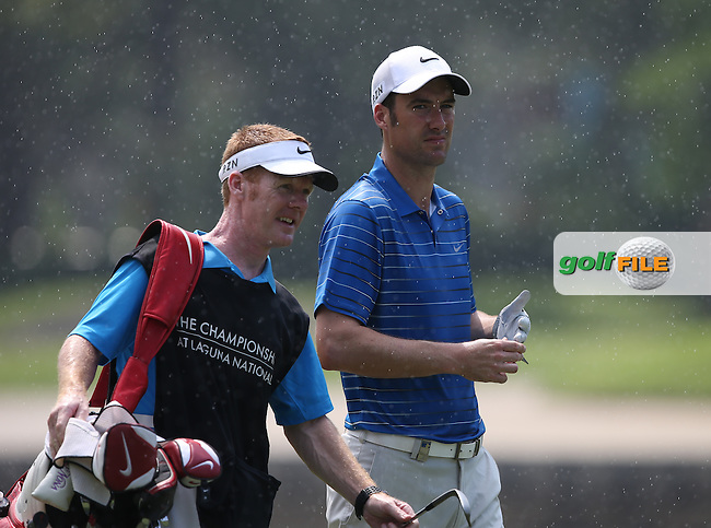 For about 10 mins the heavens opened and Ross Fisher (ENG) one of the players caught in the downpour during the Final Round of the The Championship 2014 from the Laguna National Golf & Country Club, Tampines, Singapore. Picture:  David Lloyd / www.golffile.ie