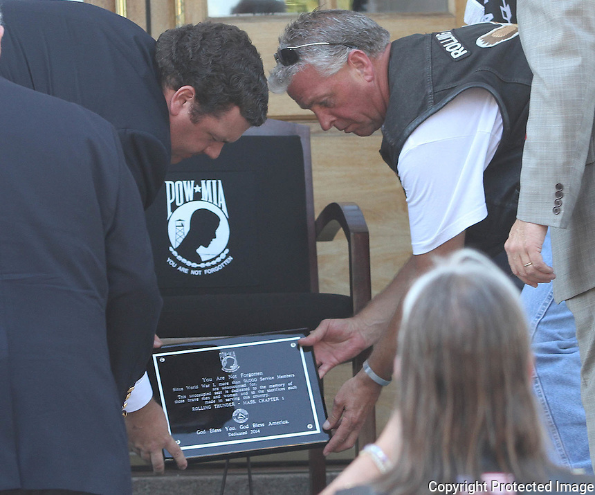 Councilor Sean Powers and Rolling Thunder President Joe D'Entremount place a plaque at the foot of the chair during the POW/MIA Chair of Honor dedication ceremony at the Braintree Town Hall Sunday September 27, 2014.(Photo by Gary Wilcox)