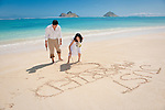 "Asian bride writes ""Just Married"" in the sand during a stroll on Lanikai beach, Mokulua Islands in the background. The couple celebrate their wedding with a honeymoon in Hawaii."