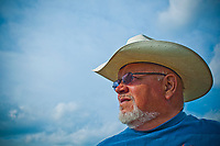 Alpaca farmer wearing white cowboy hat and blue shirt  portrait in afternoon sun with blue sky and light clouds.