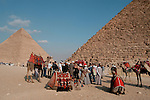 CAIRO - NOVEMBER 30, 2004 : A group of foreign tourists visiting the 5000 years old Giza pyramids in Cairo is set upon by a group of camel drivers and sellers trying to get their share of the tourist business, on November 30, 2004. Situated high on a desert plateau overlooking sprawling Cairo, Giza is the most visited tourist site in Egypt ,with the Sphinx and the 481ft high great Pyramid. Tourism has been on the decline in Egypt following a series of terrorist attacks targeting foreign tourists. (Photo by Jean-Marc Giboux)