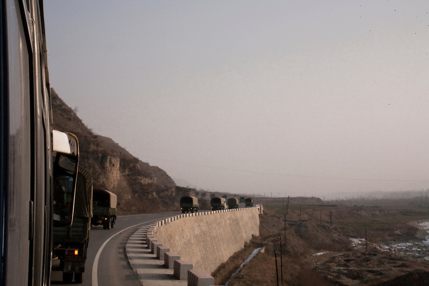 A convoy of military vehicles transporting troops of the People's Armed Police (ch: Wujing) on the road to the tibetan mountains in the province of Gansu. Dec 2009