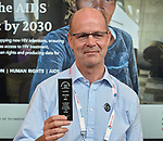 Tim Martineau, acting executive director of UNAIDS, holds material about Thursdays in Black during a July 26 seminar in the Global Village of the 2018 International AIDS Conference in Amsterdam, Netherlands. The presentation was co-sponsored by the World Council of Churches Ecumenical Advocacy Alliance.