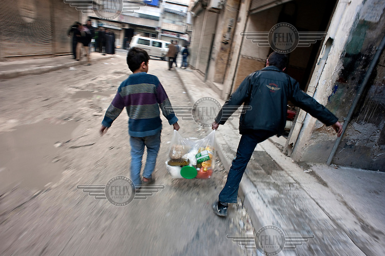 Two boys carry food through a residential street in Aleppo during a lull in the fighting. Aleppo has been engulfed by fighting between the Syrian Army and rebel fighters since the middle of 2012 leaving many residents stranded, without electricity, heating and struggling to find food.Protests against the regime of Bashar al-Assad erupted in March 2011. Although initially peaceful, they were violently repressed by the Syrian army and police. In response to being ordered to shoot unarmed civilians, large numbers of men deserted and formed the core of the Free Syrian Army (FSA) which was soon joined by civilian volunteers. Since early 2012 the protest movement has escalated into an armed uprising that many consider a civil war. Sustained fighting is ongoing throughout Syria between the regular army and its allied militias and the Free Syrian Army as well as other anti-regime groups, some of which include foreign jihadists.