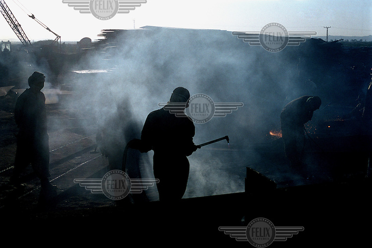 Workers weld large pieces of metal at the ship-breaking yard in Gaddani.