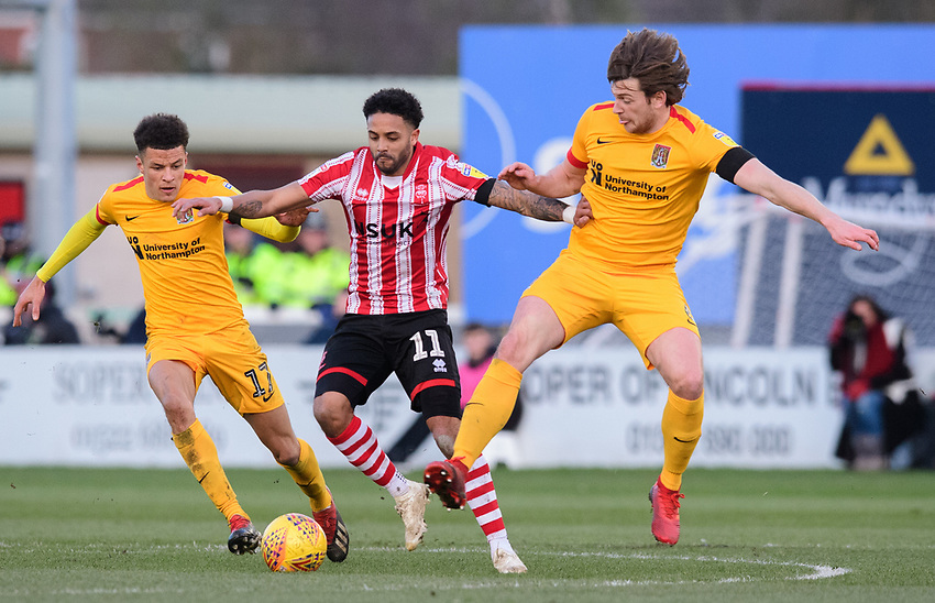 Lincoln City's Bruno Andrade under pressure from Northampton Town's Shaun McWilliams, left, is fouled by Northampton Town's Ash Taylor<br /> <br /> Photographer Chris Vaughan/CameraSport<br /> <br /> The EFL Sky Bet League Two - Lincoln City v Northampton Town - Saturday 9th February 2019 - Sincil Bank - Lincoln<br /> <br /> World Copyright © 2019 CameraSport. All rights reserved. 43 Linden Ave. Countesthorpe. Leicester. England. LE8 5PG - Tel: +44 (0) 116 277 4147 - admin@camerasport.com - www.camerasport.com