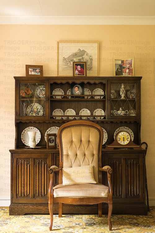 Domestic room interior with old sideboard decorated with plates, photos and a clock and an empty lounge chair
