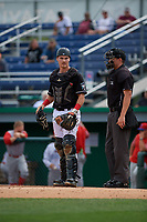 Umpire Jesse Busch and Batavia Muckdogs catcher Gunner Pollman (7) during a NY-Penn League game against the Williamsport Crosscutters on August 27, 2019 at Dwyer Stadium in Batavia, New York.  Williamsport defeated Batavia 11-4.  (Mike Janes/Four Seam Images)
