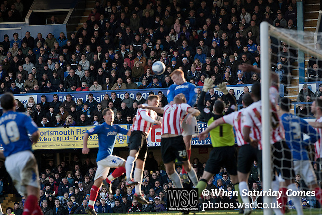 """Portsmouth 1 Southampton 1, 18/12/2012. Fratton Park, Championship. Fans in the South Stand watching the action as Portsmouth striker Dave Kitson leaps above Southampton goalkeeper Kelvin Davis during the second half of their Championship fixture at Fratton Park stadium, Portsmouth. Around 3000 away fans were taken directly to the game in a fleet of buses in a police operation known as the """"coach bubble"""" to avoid the possibility of disorder between rival fans. The match ended in a one-all draw watched by a near capacity crowd of 19,879. Photo by Colin McPherson."""