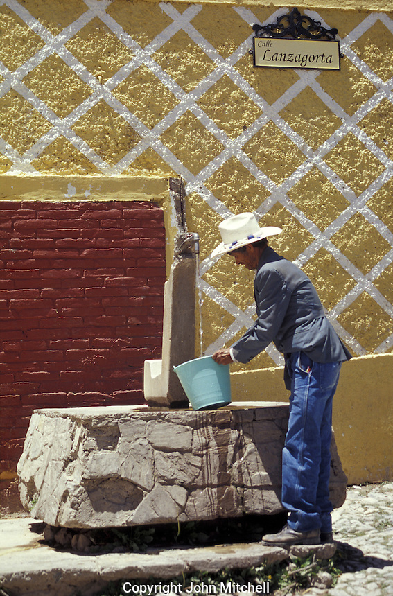Mexican man filling a pail at a commuinity tap in the 19th-century silver-mining town of Real de Catorce, San Luis Potosi state, Mexico. Real de Catorce became a virtual ghost town during the early part of the 20th century. It has recently become a popuar destination for travellers.