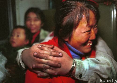 Wei's wife (R) is hugged by a friend during a two-day train ride to the city of Chengdu. Her son (L) sits in the arms of another friend...Wei is taking his wife and two children home to Sichuan on a train after living in the garbage dump for one year. He plans to put his children to school before returning alone to look for work in Beijing. The 40-hour train ride will be followed by a day-long bus journey and a three-hour-walk through the mountains...Picture taken April 1999.Copyright Justin Jin