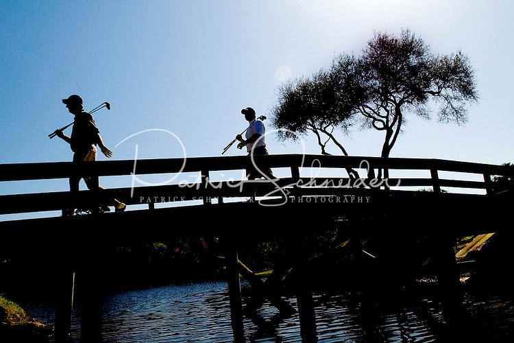 Two golfers walk across a bridge to the next hole in Amelia Island, FL