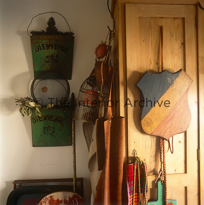 A wooden shield hangs on the door of a built-in cupboard and next to it are two steel wall planters hanging on the wall.
