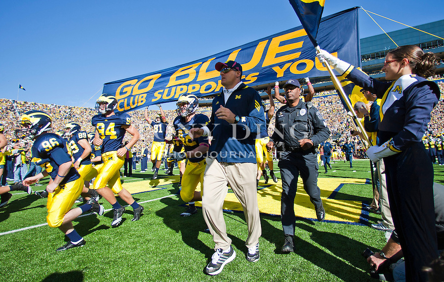 "Michigan players and head coach Rich Rodriguez, center, take the field by running under the traditional ""GO BLUE"" banner before an NCAA college football game with Iowa, Saturday, Oct. 16, 2010, in Ann Arbor, Mich. (AP Photo/Tony Ding)"
