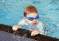 Jongen met zwembrilletje krijgt zwemles