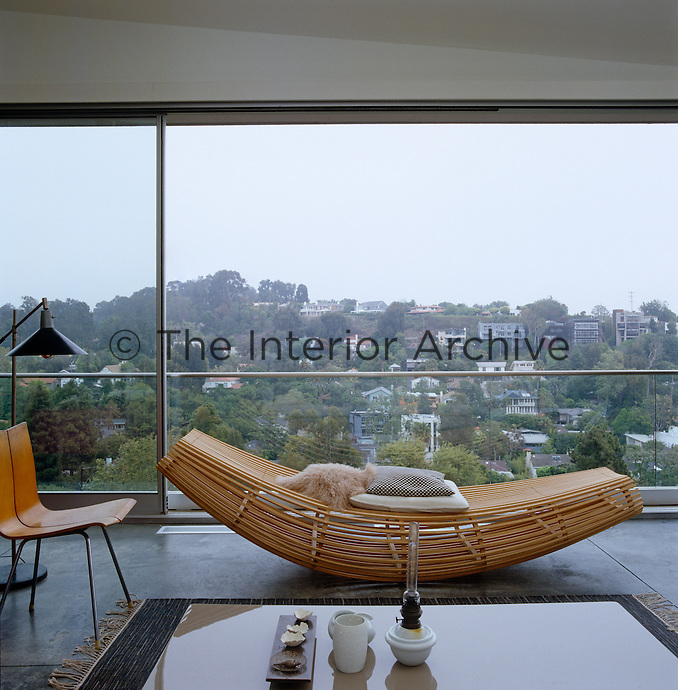 A sculpted bamboo chaise longue in this living room is situated against a plate-glass window with a spectacular view