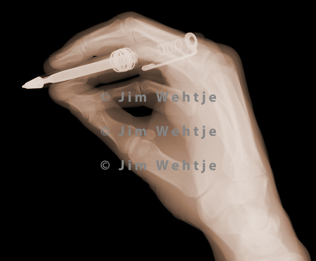 X-ray image of a hand holding a pen (brown on black) by Jim Wehtje, specialist in x-ray art and design images.