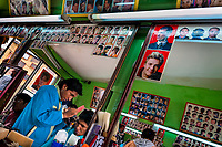 A young Bolivian hairdresser cuts a customer's hair in a barber shop in El Alto, Bolivia, 11 February 2014.