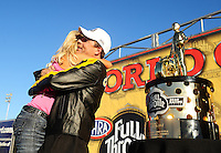 Nov 13, 2010; Pomona, CA, USA; NHRA pro stock driver Greg Anderson (right) celebrates with wife Kim Anderson after clinching the 2010 pro stock championship during qualifying for the Auto Club Finals at Auto Club Raceway at Pomona. Mandatory Credit: Mark J. Rebilas-