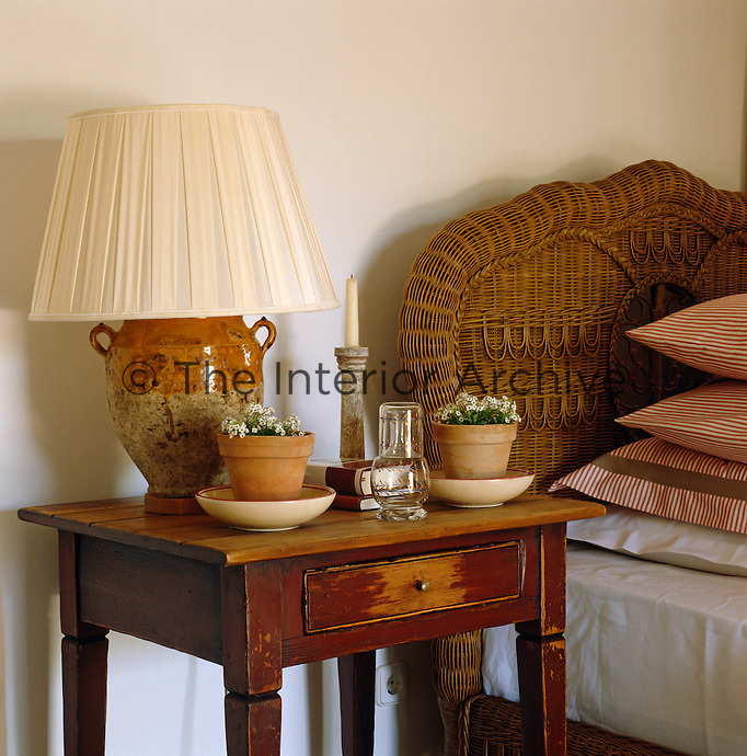 A pair of small terracotta pots on a rustic bedside table beside a bed with a wicker headboard